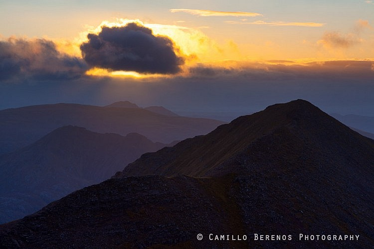 Crepescular rays above An Teallach as the sun is obscured by a fast moving cloud.