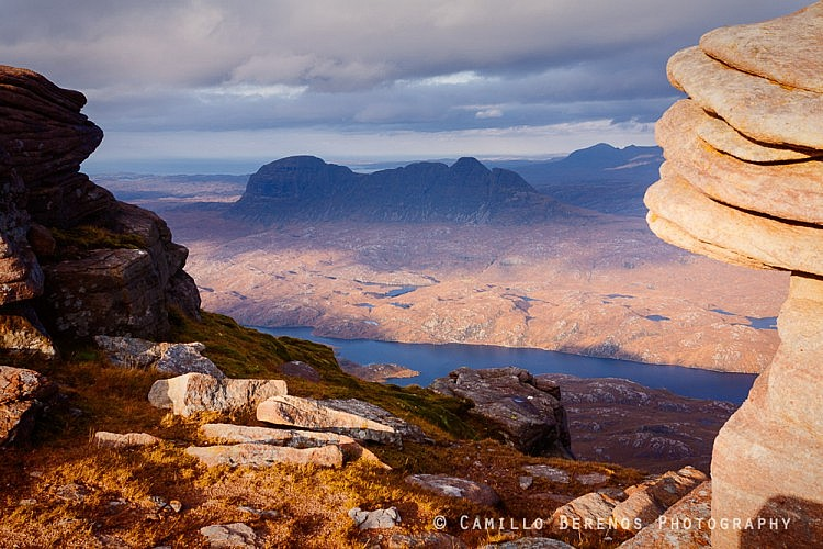 Torridonian rock forations on Cul Mor framing Suilven in the background.