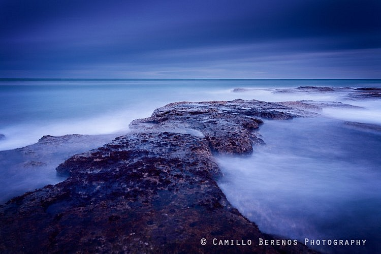 Large waves pounding the reef at Thorntonloch during the blue hour before sunrise.