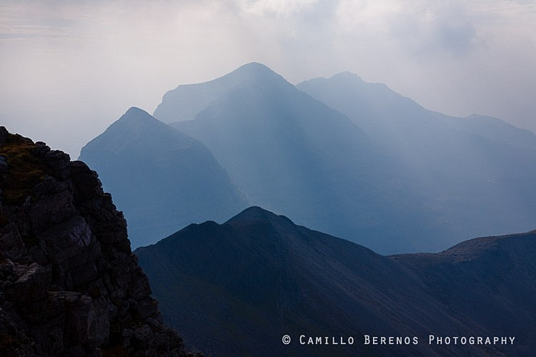 Liathach looming behind the impressive ridge of Beinn Eighe. While it was very hazy, this worked quite well in combination with the backlight and the rays of light cutting trough the clouds.