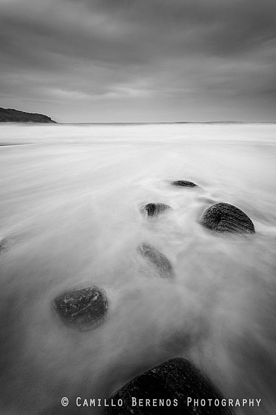 Stones lie on the beautiful sandy beach of Dail Mor as the tide comes in.